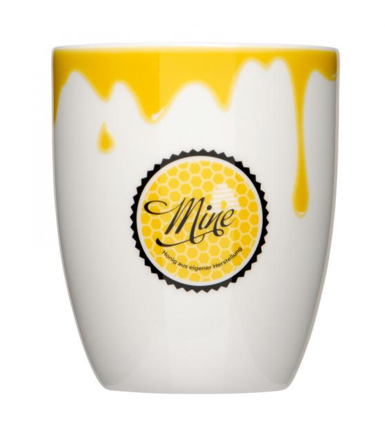 weisse Tasse mit gelbem Logoaufdruck